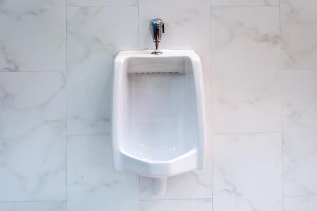 Vecchi orinatoi bianchi nel bagno degli uomini