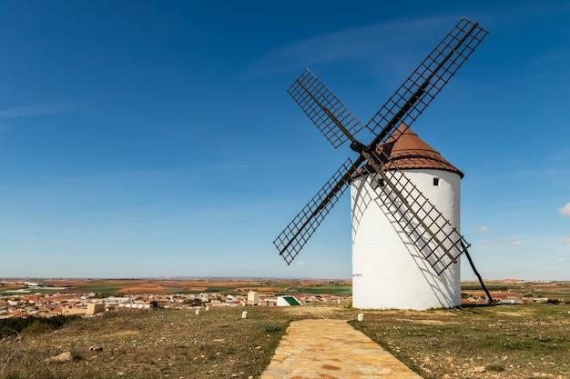 Vecchi mulini a vento bianchi, fatti di pietra, sul campo con cielo azzurro e nuvole bianche. la mancha, castilla, spagna. europa.