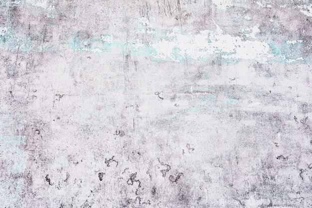 Vecchio bianco con struttura blu che si stacca dal muro di cemento per lo sfondo