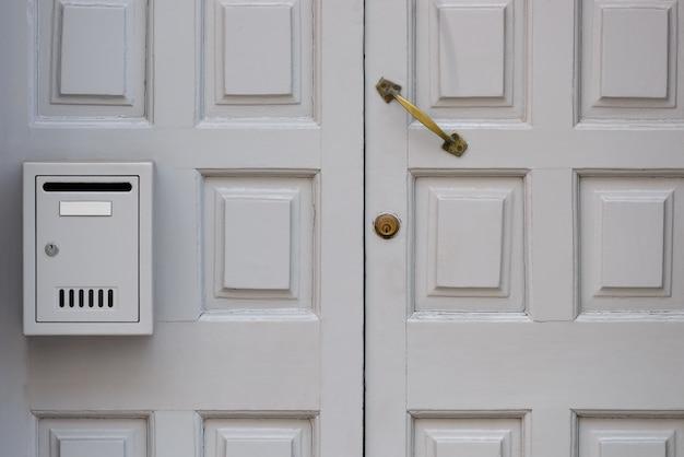 Vecchia porta di legno bianca con il primo piano della cassetta postale