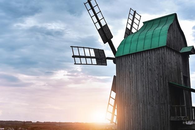 Vecchio mulino a vento in piedi da solo nel campo con il cielo blu sullo sfondo con copyspace