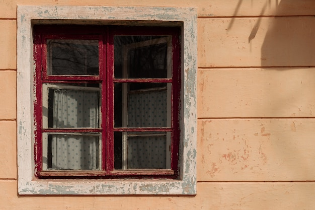 Vecchia finestra in casa abbandonata con cornice rossa in legno e tenda