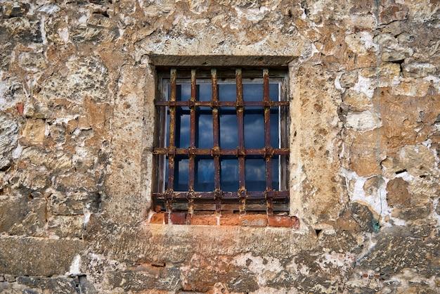 Una vecchia finestra nel castello con una grata d'acciaio arrugginita