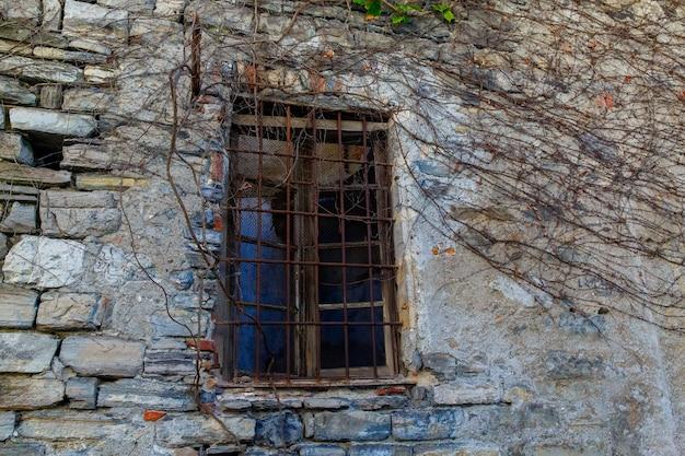Una vecchia finestra in una casa di pietra su una strada a varenna, una piccola cittadina sul lago di como, italy