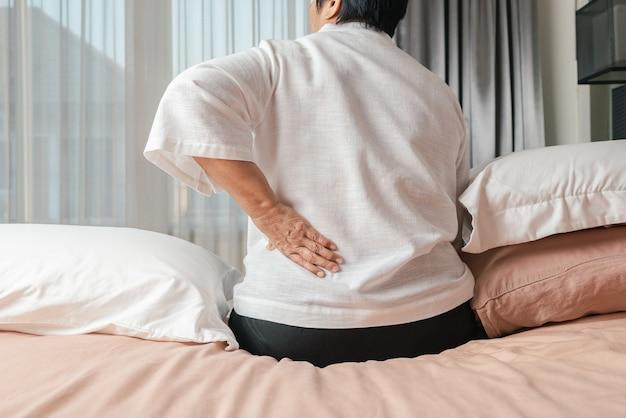 Vecchia donna mal di schiena a casa, concetto di problema di salute