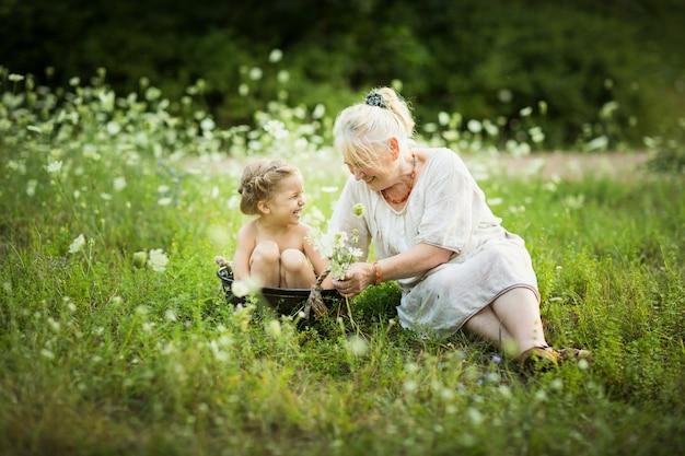 Vecchia donna bagno bambina in un bacino all'aperto in una giornata estiva intorno ai fiori