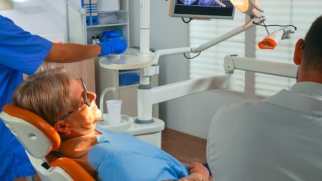 Vecchia donna al dentista che ha un trattamento dentale in ufficio di implantologia. l'ortodontista accende la lampada e parla con il paziente seduto su una sedia stomatologica mentre l'infermiera prepara gli strumenti per l'intervento chirurgico.