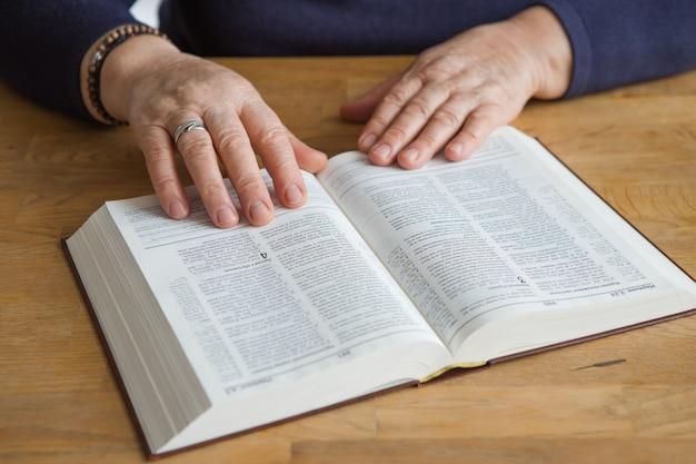 Mani dell'anziana sulla preghiera aperta bibbia dell'ucraina. leggendo il libro pregare.