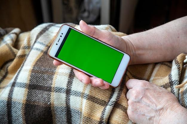 Vecchia donna mani con un telefono cellulare che chiama per la consegna o servizi di emergenza