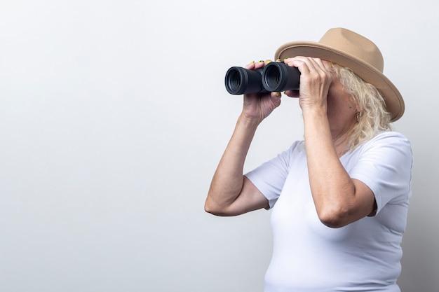 Vecchia donna in un cappello guardando attraverso il binocolo su uno sfondo chiaro.