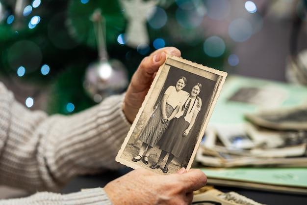 Vecchia holding della donna e vecchia foto sullo sfondo dell'albero di natale. generazioni e concetto di valori di vita.