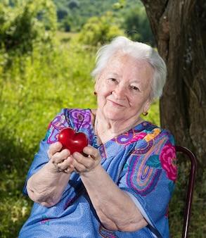 Vecchia donna che tiene cuore rosso nelle mani all'aperto