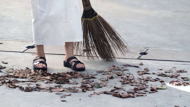 La vecchia donna sta spazzando le foglie secche sul pavimento di cemento all'aperto con una grande scopa lunga.
