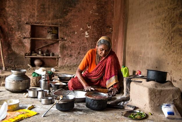 Vecchia donna che prepara e cucina la cottura di cibi freschi in un villaggio rurale in una cucina vintage