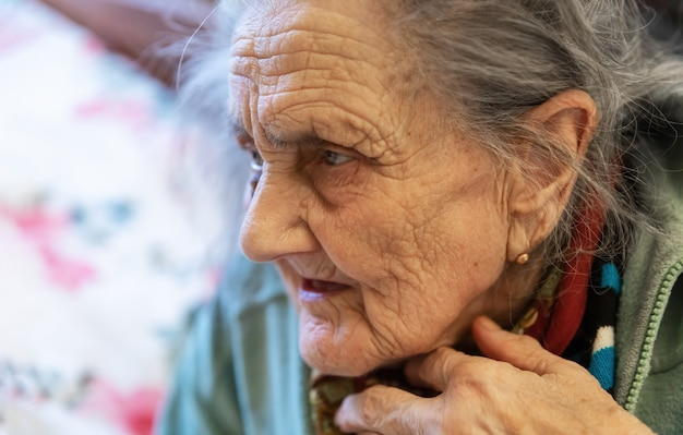 Vecchia donna. ritratto di donna molto anziana stanca in depressione seduto al chiuso sul letto