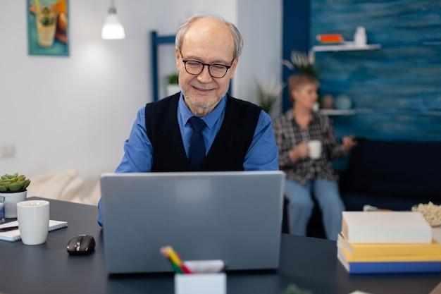 La vecchia donna che si rilassa sul divano con in mano una tazza di caffè e il marito sta lavorando. imprenditore anziano nel posto di lavoro domestico utilizzando un computer portatile seduto alla scrivania mentre la moglie tiene in mano il telecomando della tv.