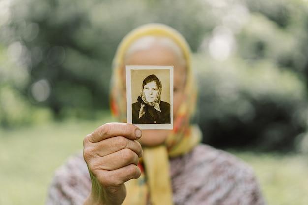 La vecchia ricorda la sua giovinezza. la nonna conserva la sua foto in gioventù. ricordi. vecchie foto d'epoca