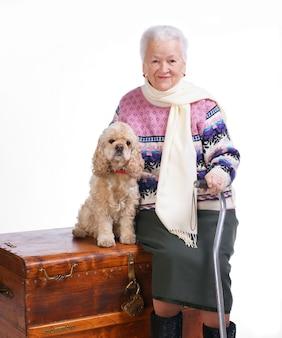 Vecchia donna seduta su una scatola con un cane su uno sfondo bianco