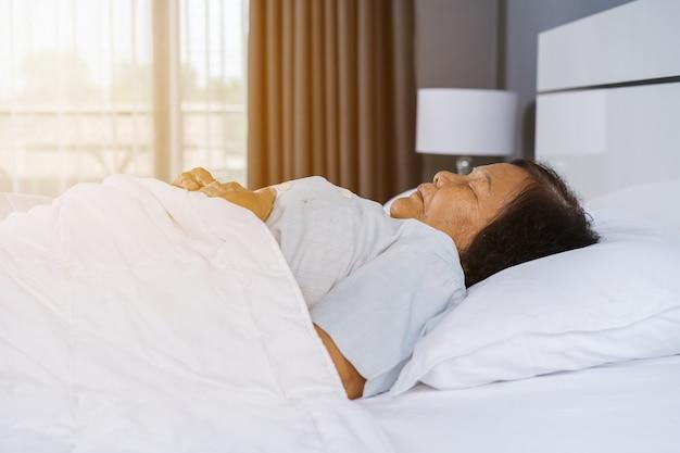 Vecchia donna che dorme su un letto in camera da letto