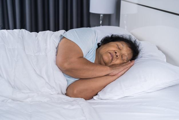 Vecchia donna che dorme su un letto
