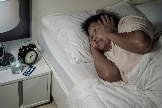 L'anziana che soffre di insonnia sta cercando di dormire nel letto di notte
