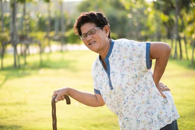 Donna anziana che cammina nel parco e che ha mal di schiena, mal di schiena.