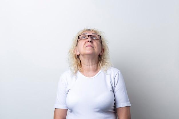 Vecchia donna con gli occhiali alzando lo sguardo su uno sfondo chiaro.
