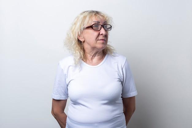 La vecchia con gli occhiali guarda di lato su uno sfondo chiaro.