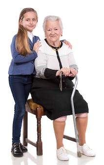 Vecchia donna con la nipote su un muro bianco