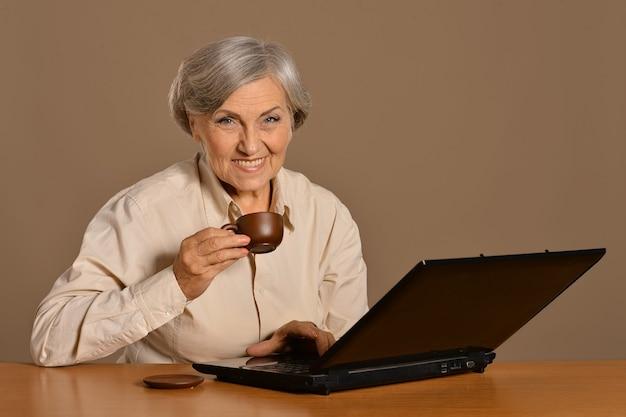 Vecchia donna con un computer portatile e caffè sullo sfondo