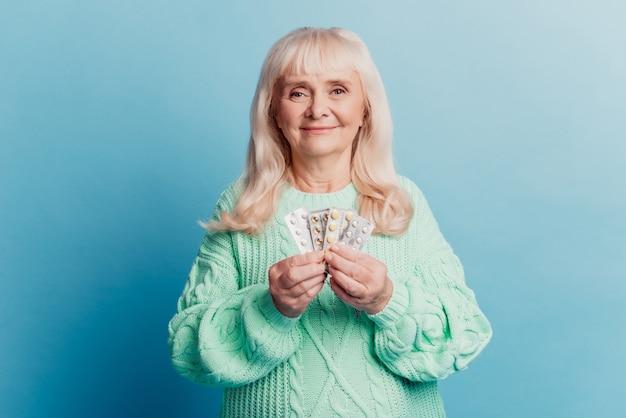 La donna anziana con il prodotto medico tiene le compresse in mano su sfondo blu