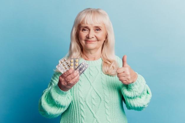La donna anziana con le compresse della tenuta del prodotto medico mostra il pollice in su su sfondo blu