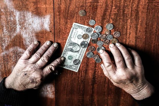 Anziana con pochissimi soldi. concetto di povertà. pensionato con una banconota da un dollaro e monete in mano. economia e crisi nel mondo.