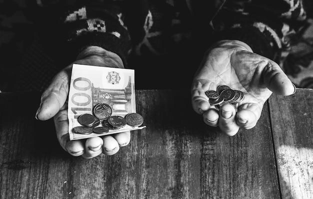 Anziana con pochissimi soldi. concetto di povertà. pensionato con una banconota in euro e monete in mano. economia e crisi nel mondo.