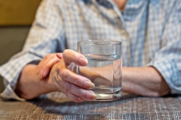 Mani delle donne anziane che tengono un bicchiere d'acqua.
