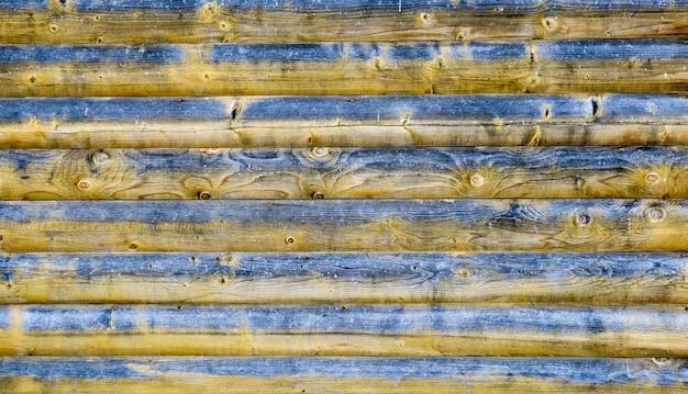 Vecchio fondo o struttura di legno. tavole orizzontali in pino vecchio. la trama del legno è nera e gialla con anelli di nodi e crepe. fondo di legno astratto.