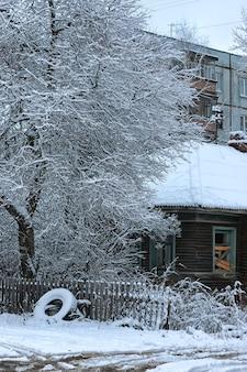 Vecchia casa di legno nell'inverno della città