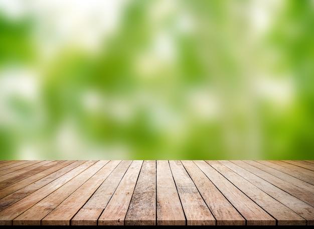 Vecchia tavola di legno con sfondo sfocato verde astratto per la visualizzazione del prodotto