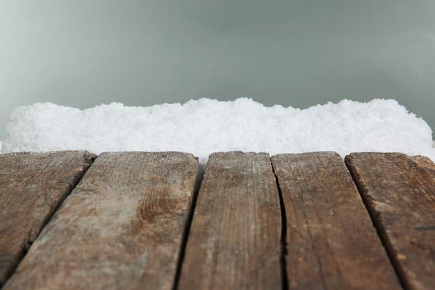Vecchie tavole di legno con neve su sfondo grigio