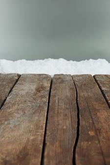 Vecchie tavole di legno con neve sulla superficie grigia