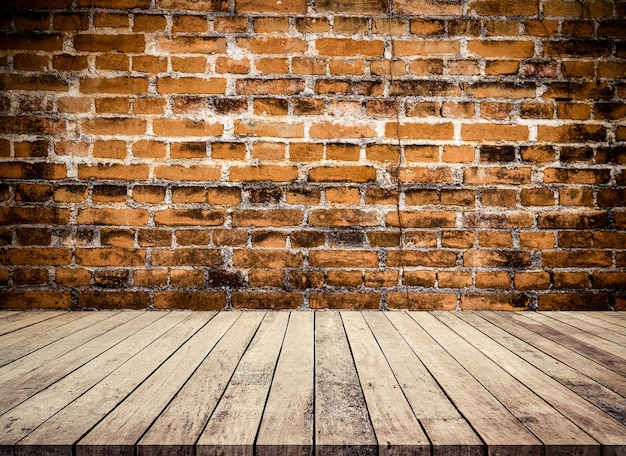 Vecchio tavolo in legno o pavimento in legno con sfondo in prospettiva di un vecchio muro di mattoni rossi per l'esposizione dei prodotti