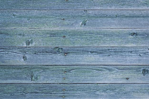 Vecchia struttura di legno naturalmente sbiadita, muro grigio con vernice squallida verde blu