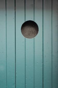 Vecchia superficie di legno dipinta di blu della porta con uno sfondo di foro rotondo