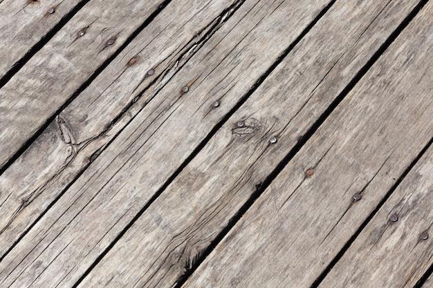 Vecchie assi di legno che presentano segni di danneggiamento e distruzione, fanno parte del pavimento di una casa o di un altro edificio