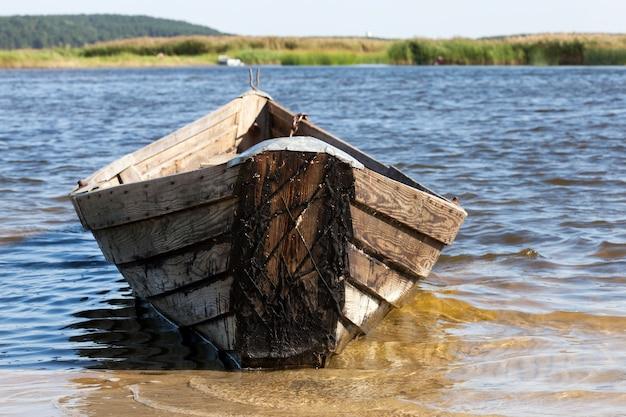 Vecchia barca in legno con vecchi attrezzi da pesca per la pesca, vecchio villaggio abbandonato