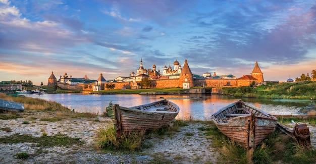 Vecchie barche di legno sulla riva della baia della prosperità sull'isola di solovetsky e una vista dei templi del monastero di solovetsky sotto i raggi del sole al tramonto