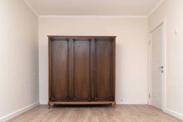Vecchio armadio in legno marrone in un moderno soggiorno ristrutturato con carta da parati dipinta