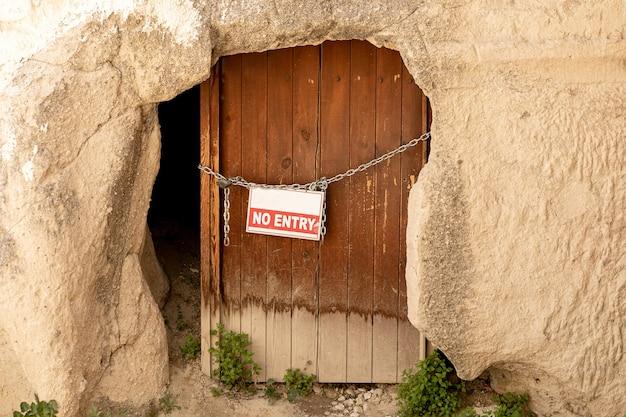 Vecchia porta d'ingresso della grotta in legno con la scritta proibito appeso a una catena con un lucchetto