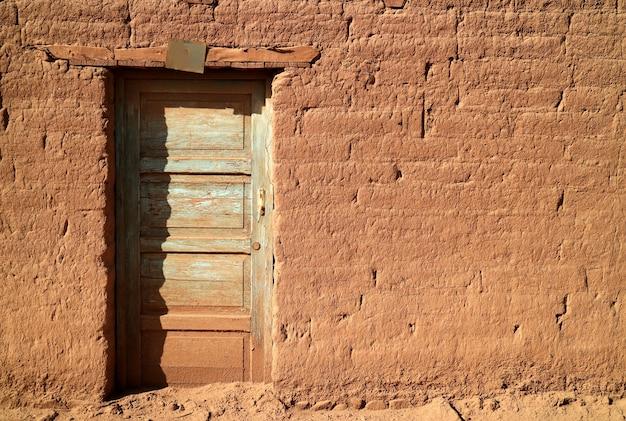 Vecchia porta di legno sulla facciata in mattoni di adobe alla luce del sole, una piccola città nel nord del cile