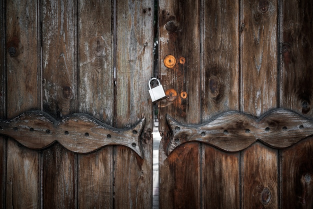Vecchia porta di legno chiusa con un lucchetto